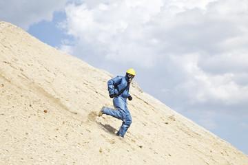 Deutschland, Bayern, Mann in Schutzkleidung läuft am Hang der Sanddüne