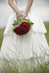 Braut, die auf der Wiese einen Strauß Blumen hält