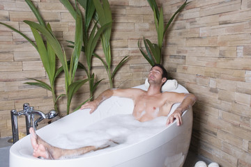 Mann liegt in der Badewanne, die Augen geschlossen