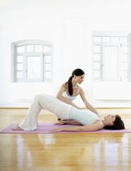 Deutschland, Hamburg, Yoga-Lehrer hilft Frau, macht Yoga-Übung im Fitnessraum