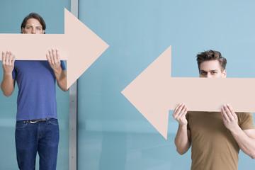 Deutschland, Nordrhein-Westfalen, Düsseldorf, Junge Männer, deren Pfeile in verschiedene Richtungen zeigen