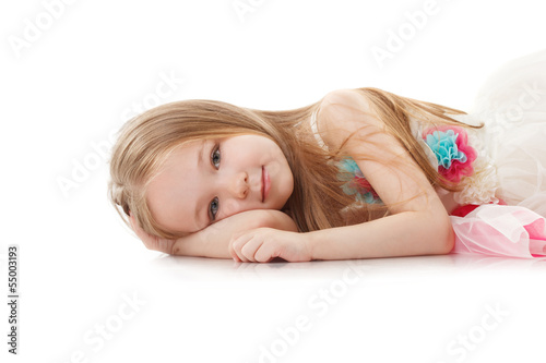 Portrait of smiling adorable girl lying in studio