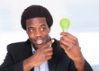 Businessman Holding Light Bulb With Green Grass