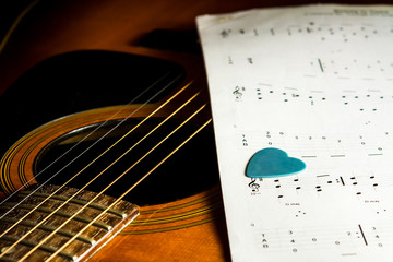 Acoustic guitar with song note paper