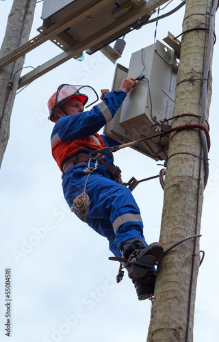 Electrician perform maintenance on the transmission towers reclo
