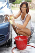 Young woman washing her car
