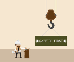Businessman control crane hanging with safety first sign