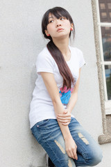 Asian girl against wall