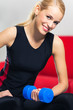 Young happy smiling woman with dumbbells