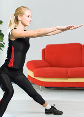 Young woman doing fitness exercise, indoors