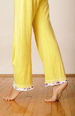 Barefoot woman in yellow pajamas