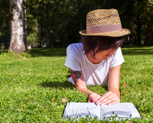 Beautiful girl hipster lies on meadow and reads the book