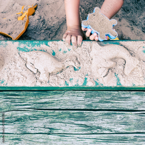 Kid creating animal forms in sandpit