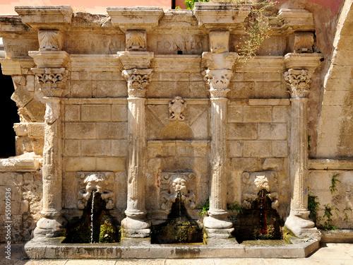 Leinwanddruck Bild Old venetian fountain in city of Rethymno, Crete, Greece