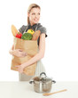 Woman in apron holding grocery bag, standing near table with pan