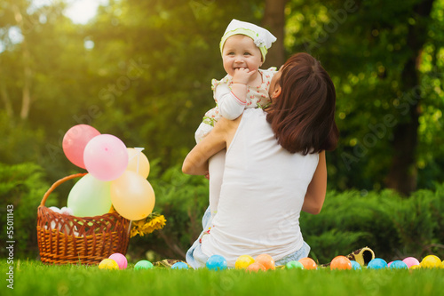 cute baby and mom are playing on the green grass