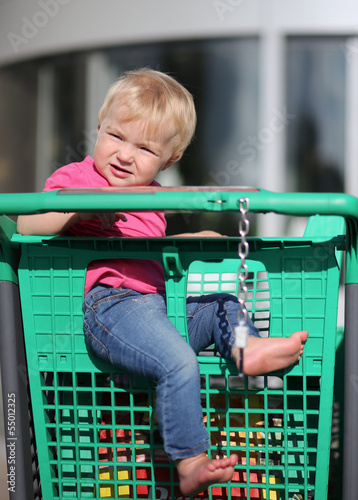 Cute baby girl sitting in a shopping trolley at supermarket