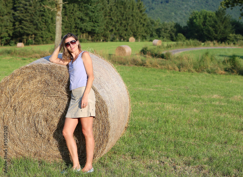Young pregnant woman standing next to hay bale