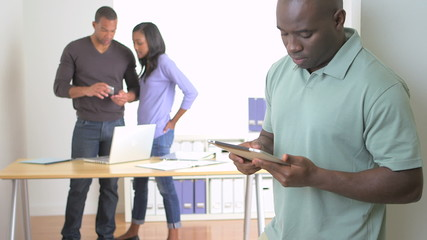 Confident black businessman standing with tablet