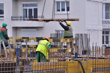 Ouvriers sur chantier en action au sommet de la construction