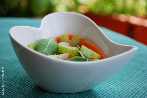 Vegetables salad in heart shape bowl on green natural background