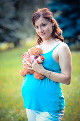 Young happy and smiling woman with teddy bear is waiting baby