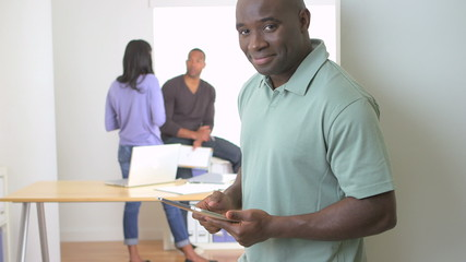Happy back businessman standing with tablet