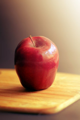 Red apple on the wooden board