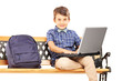 Schoolboy sitting on a wooden bench with school bag next to him