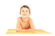 Smiling shirtless child lying on a beach towel