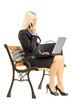 Young busy businesswoman sitting on bench and working on laptop