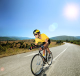 Male cyclist riding a bike on an open road on a sunny day
