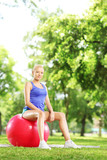 Young blond female sitting on a pilates ball