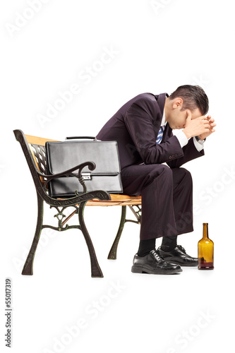 Disappointed young businessperson sitting on a wooden bench