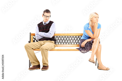 Young couple sitting on a wooden bench after having an argument
