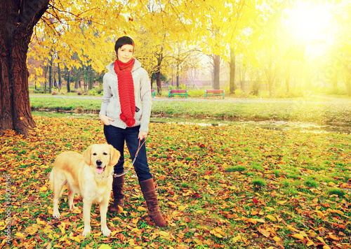 Young female and her dog posing in autumn in a park