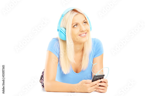 Young relaxing female lying and listening music