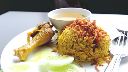 chicken curry with pilau rice on white plate