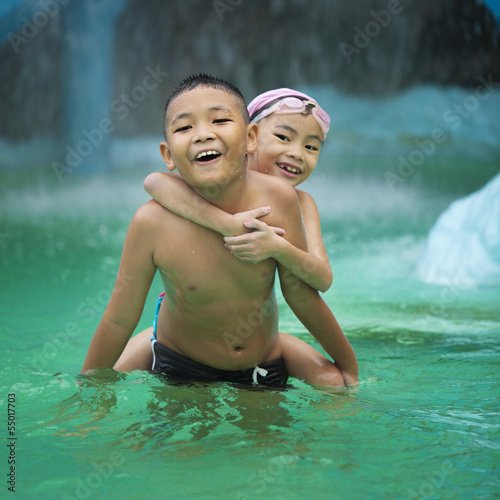 Happy Asian kids having fun at swimming pool