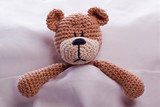 brown teddy bear lyiing sick in bed