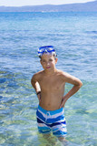 Cute eleven years old boy staying in the sea