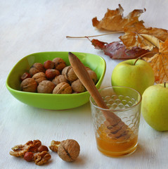 Nuts, honey and apples on a background of yellow leaves.