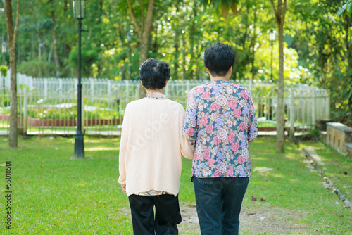 Rear view Asian old mother and senior daughter walking at outdoo