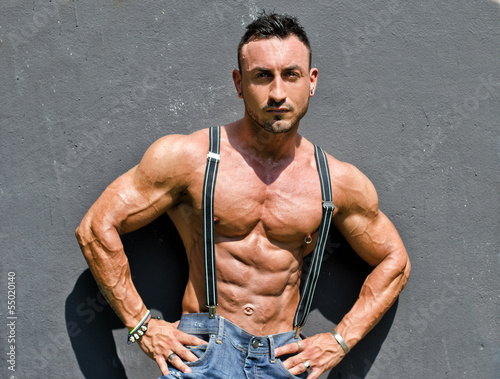 Muscle man with jeans and suspenders on grey wall