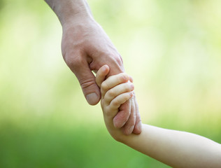 Hands of man and child holding together