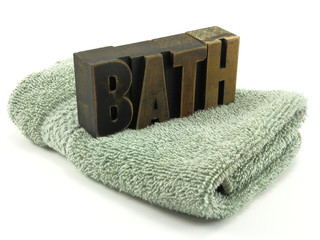Single green wash cloth and vintage letterpress bath