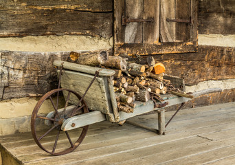 Rustic wheel barrow carrying fire wood on a log cabin porch