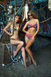 Two swimsuit models posing sexy in front of graffiti background