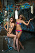Two swimsuit models posing sexy in front of graffiti