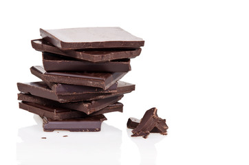 Dark chocolate pieces in stack over white background